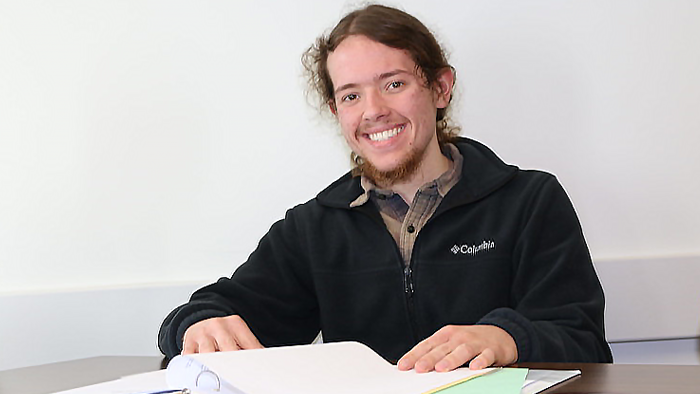 A student sitting at a table with a binder open, smiling at the camera