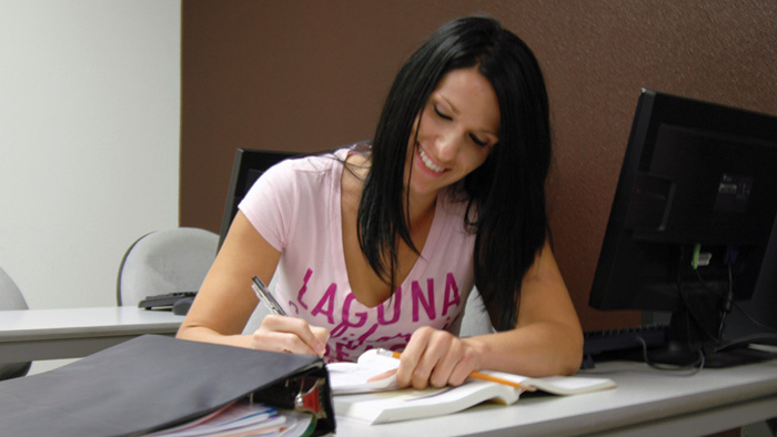 Female smiling and writing in MSU evening class
